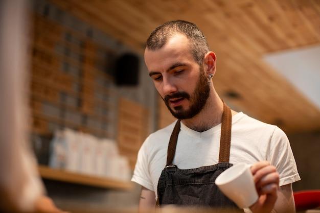 Close-up do homem com avental segurando o copo vazio