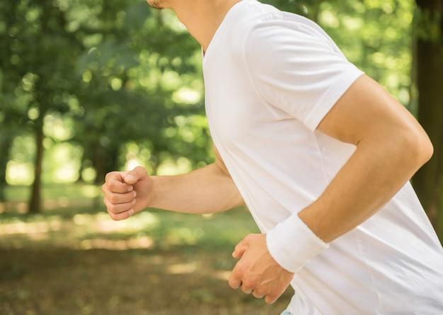 Close-up do homem correndo ao ar livre pela manhã.