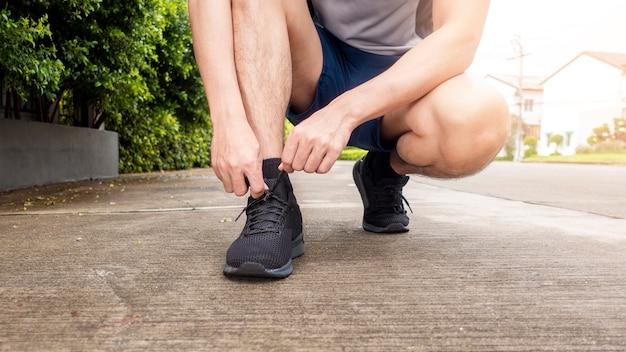 Close-up do homem de aptidão é amarrar sapatos