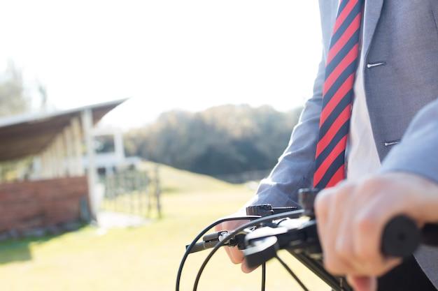 Close-up do homem de negócios com sua bicicleta