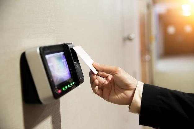 Close-up do homem de negócios da mão using keycard to open door.