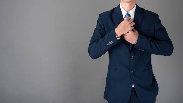 Close-up do homem de negócios de terno azul é confiante em fundo cinza