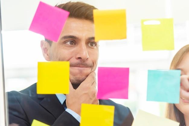 Close up do homem de negócios que pensa e que olha ao bloco de notas na janela de vidros.