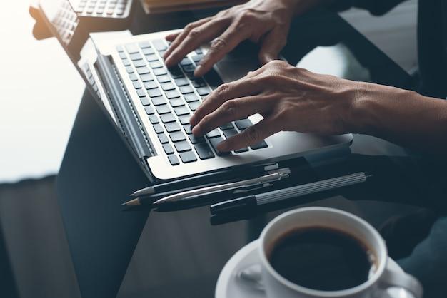 Close-up do homem de negócios, trabalhando no computador portátil