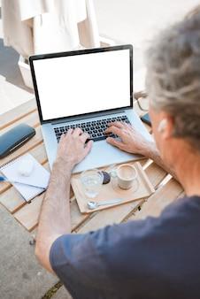 Close-up do homem digitando no laptop com café e copo de água na mesa de madeira