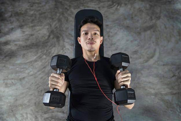 Close-up do homem fitness, treino de cara bonito e atlético com halteres, vista superior