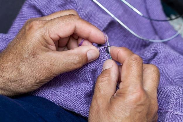 Close up do homem idoso que faz malha uma camisola roxa. tricô como passatempos feitos à mão.