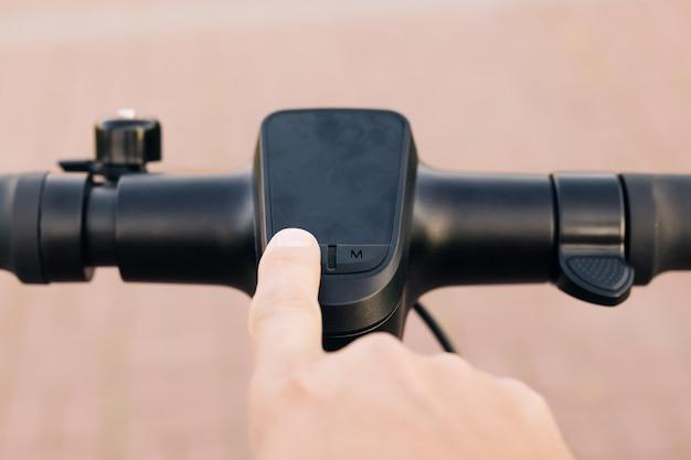 Close-up do homem moderno liga a scooter elétrica. o homem está apertando o botão iniciar do gadget moderno