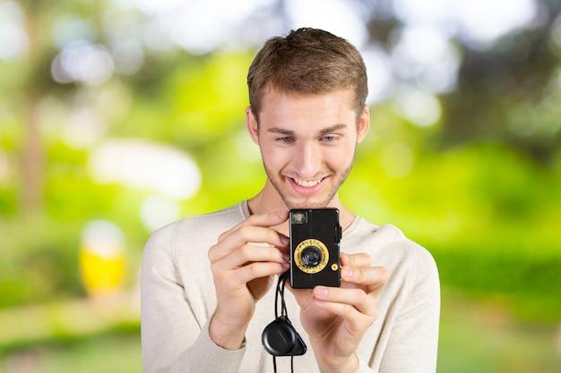 Close up do homem novo do moderno com câmara digital ao ar livre.