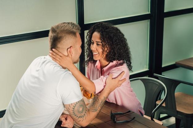 Close up do homem novo que beija sua mão da esposa ao fazer a proposta de casamento ao ar livre.