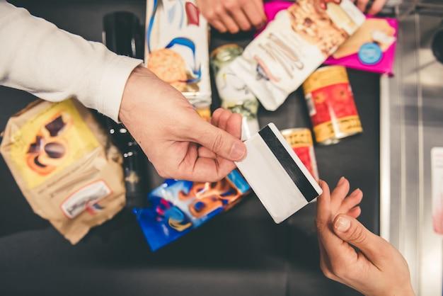 Close-up do homem que dá um cartão de crédito no balcão de caixa.