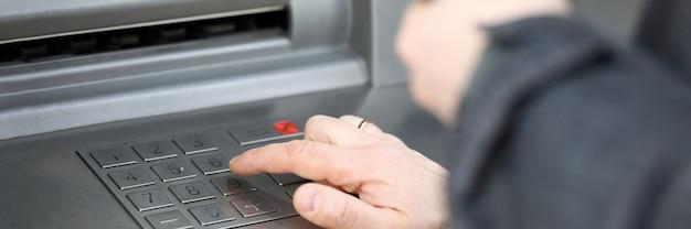 Close-up do homem que pressiona o código pin na máquina de dinheiro ao ar livre. pessoa recebendo salário ou pensão. cartão de crédito e caixa eletrônico. dinheiro e conceito de estabilidade financeira