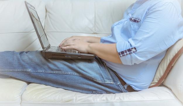 Close-up do homem que trabalha com computador portátil e sentado no sofá em casa