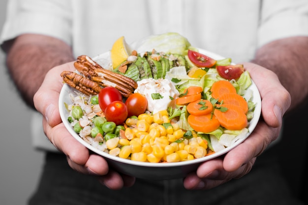 Close-up do homem segurando a tigela de comida saudável
