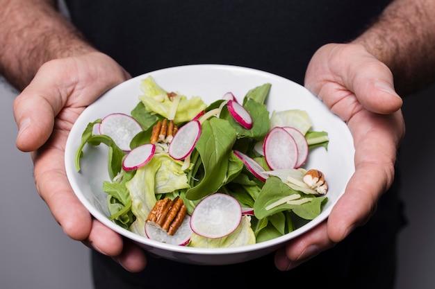 Close-up do homem segurando a tigela de salada nas mãos