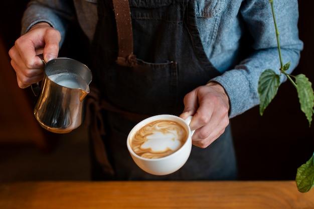 Close-up do homem segurando a xícara de café com leite