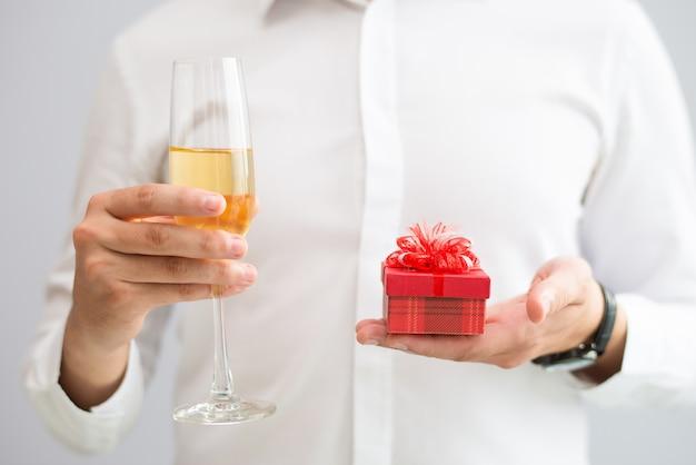 Close-up do homem segurando o copo com champanhe e pequena caixa de presente