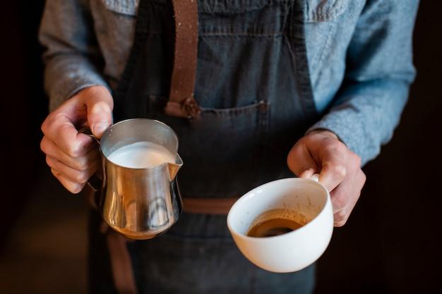 Close-up do homem segurando o leite e a xícara de café