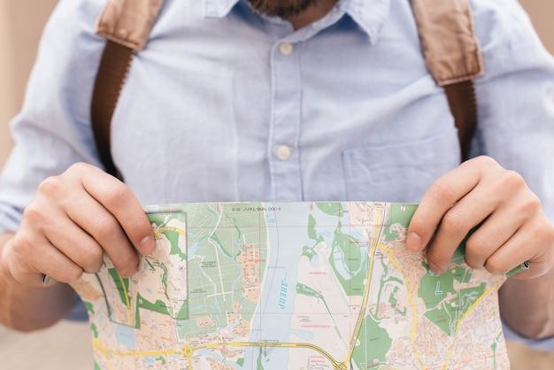 Close-up do homem segurando o mapa enquanto viaja