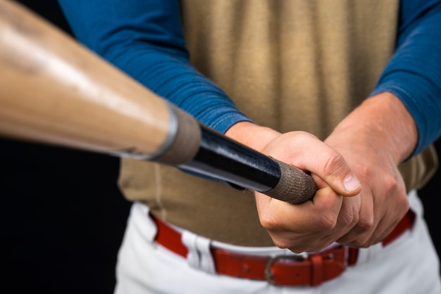 Close-up do homem segurando o taco de beisebol desfocado