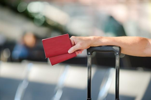 Close-up do homem segurando passaportes e cartão de embarque no aeroporto