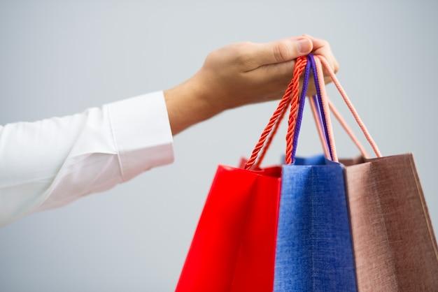 Close up do homem segurando sacolas de compras