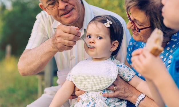 Close-up do homem sênior alimentando-se com purê de frutas a adorável menina sentada sobre uma mulher sênior em um banco ao ar livre. conceito de estilo de vida de avós e netos.