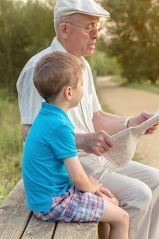 Close-up do homem sênior e do menino bonito, lendo um jornal sentado no banco do parque. concentre-se na criança.