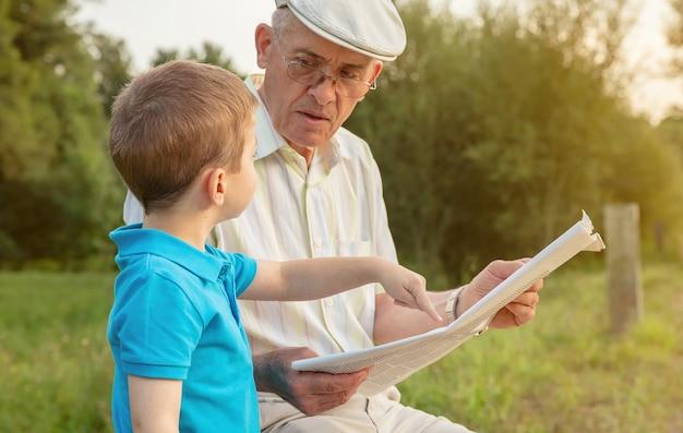 Close-up do homem sênior lendo jornal e criança bonita apontando um artigo com o dedo sentado sobre um fundo de natureza. conceito de duas gerações diferentes.