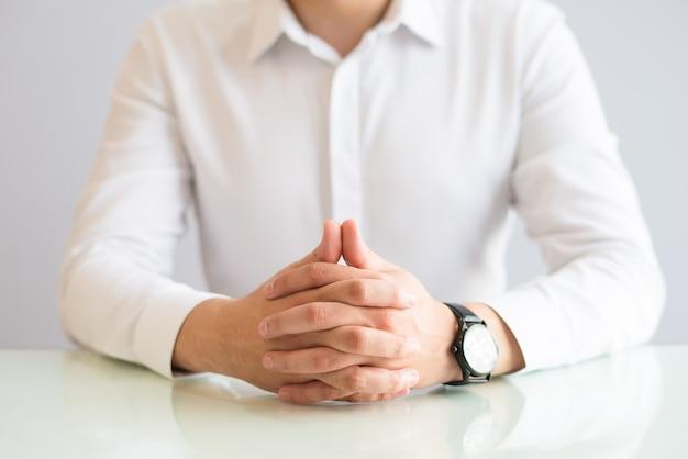Close up do homem sentado à mesa com as mãos entrelaçadas
