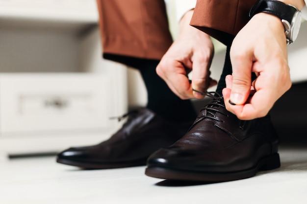 Close-up do homem sentado na cama e usando sapatos de casamento