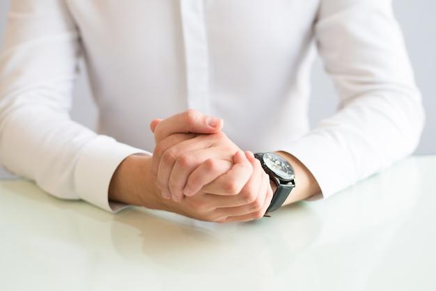 Close up do homem sentado na mesa com as mãos entrelaçadas