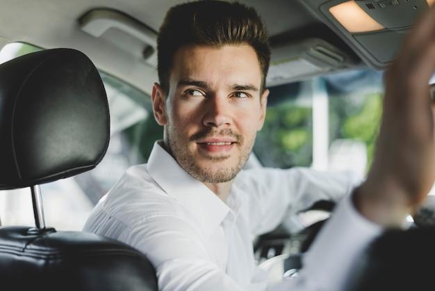 Close-up do homem sentado no carro olhando para trás
