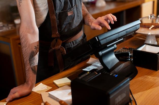 Close-up do homem trabalhando na caixa registradora