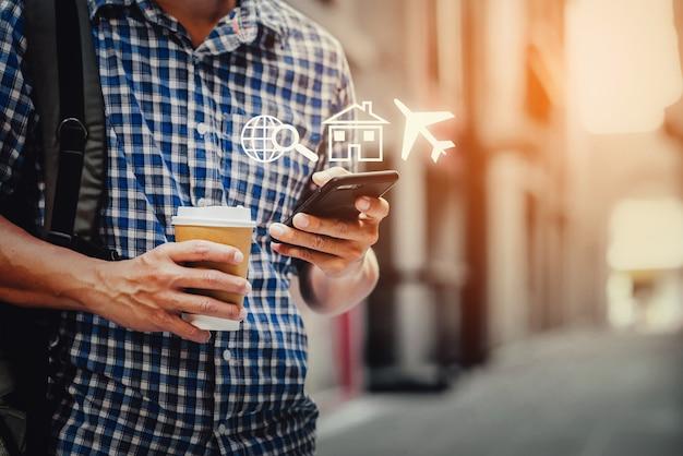 Close up do homem usando seu telefone celular e xícara de café na rua