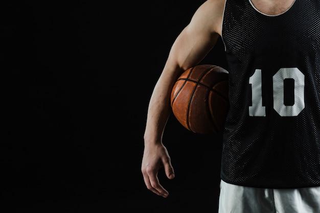 Close-up do jogador de basquetebol com bola debaixo do braço