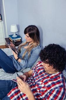 Close-up do jovem casal apaixonado, usando dispositivos eletrônicos, enquanto descansava sobre uma cama. tempo de lazer no conceito de casa.