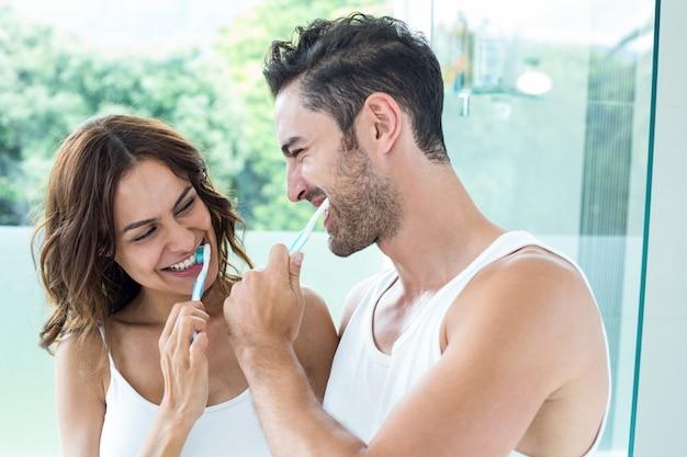 Close-up do jovem casal escovar os dentes