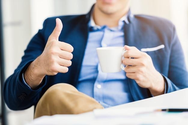 Close-up do jovem empresário de humor feliz, mostrando os polegares para cima trabalhando com segurando uma xícara de café, sentar-se à mesa