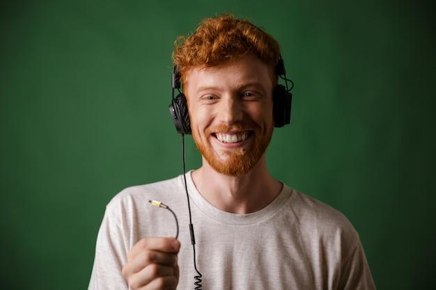 Close-up do jovem hipster readhead encaracolado segurando o cabo dos fones de ouvido