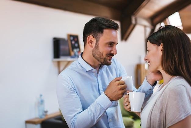 Close-up do lindo casal jovem olhando uns aos outros e sorrindo enquanto desfruta de café no café juntos