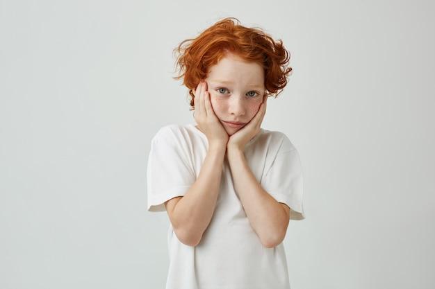 Close-up do lindo menino com cabelos ruivos e sardas de mãos dadas nas bochechas, olhando, estar cansado