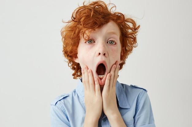 Close-up do lindo menino ruivo com cabelos cacheados, segurando as mãos nas bochechas, estar com medo