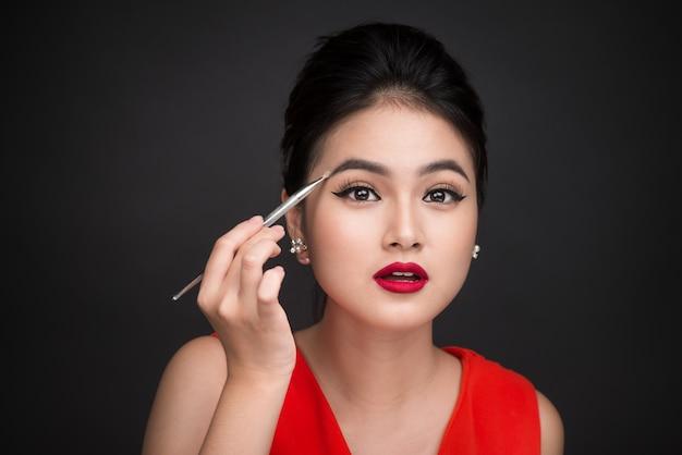 Close-up do lindo rosto de uma jovem mulher asiática aplicando a sombra na sobrancelha com um pincel