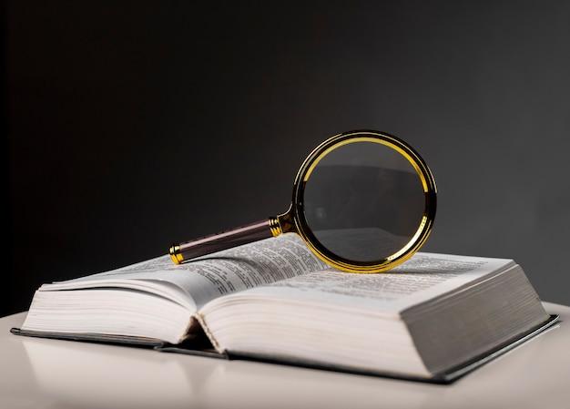 Close up do livro aberto com páginas viradas e lupa. livro de capa dura na mesa. conceito de estudo e pesquisa.