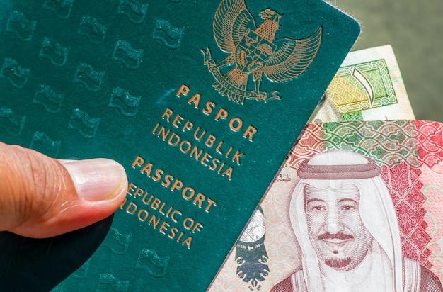 Close-up do livro do passaporte verde da indonésia e do rial saudita, a moeda da arábia saudita, para a preparação de peregrinos da indonésia