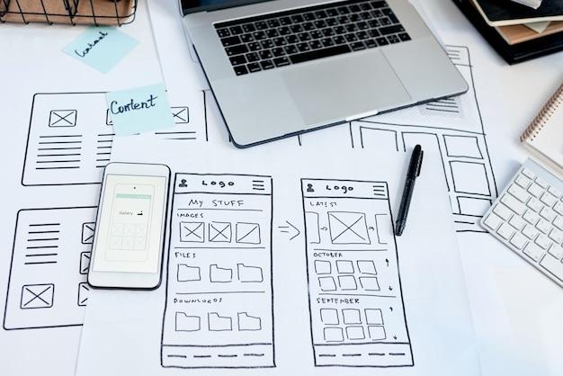 Close-up do local de trabalho do designer de interface do usuário, criando um aplicativo utilizável para dispositivos, esboços e smartphone na mesa