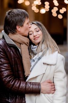 Close-up do marido beija a esposa enquanto caminhava pela cidade