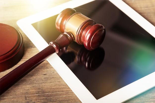 Close-up do martelo de madeira no tablet digital. conceito de justiça