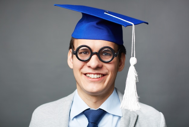 Close-up do menino inteligente com tampão da graduação